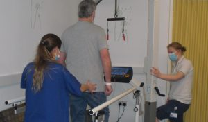 Patient using Stroke Rehabilitation treadmill with support from Physio team